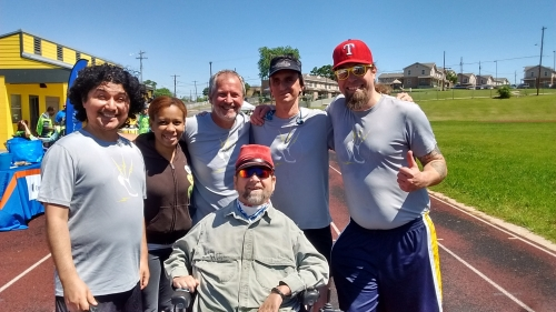 On an outdoor track, a group of smiling people of various ages stand shoulder to shoulder; a man in a power chair is in front.