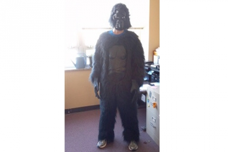 A person in a gorilla suit and mask stands next to a desk.
