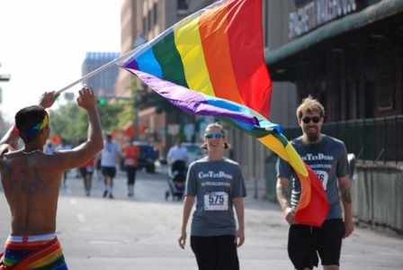 A woman and man in matching running shirts walk down a street as a rainbow flag flags in the foreground.