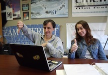 At an open laptop, a man makes an emphatic thumbs down while a young woman next to him gives a thumbs up.