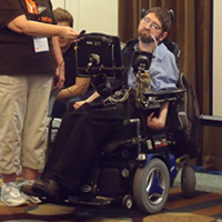 A man sits in a power chair, eyes cast down at a screen, while a microphone is held up to his speaking device.