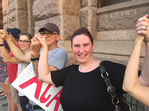 Erin smiles at the camera from a line of people with upraised, joined hands. The stone façade of the Texas Capitol is right behind them.