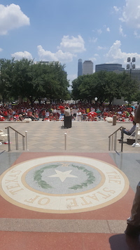From behind, a man at a podium holds an arm in the air as he addresses a crowd. They are outside, and in the foreground, is the seal of the State of Texas in marble flooring.