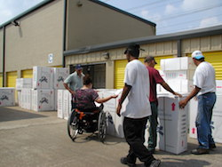Outside a warehouse with stacks of white boxes, a woman sitting in a wheelchair with her back to camera looks through papers, while several men move boxes.