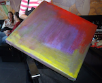 A painting with swaths of yellow, purple-blue, and red paint sits on one of its corners in a director's chair.