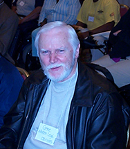 A man with white hair and beard smiles up at the camera from a folding chair among a big group seated people.