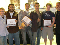 Six men, five college-age and one older, stand in a line holding up certificates, smiling broadly at the camera.
