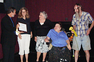 A man hands a plaque to a smiling woman. Next to her are three people smiling and looking on, one sitting in a power chair, another holding a yellow flower.