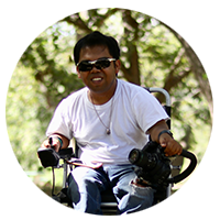 In a shady wooded area, a man with sunglasses sitting in a power chair smiles at the camera.