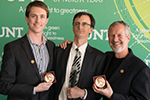 Three men in suits smile broadly at the camera. Two hold bronze, circular awards and the other grips a white cane.