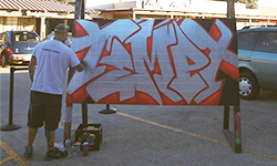 A man with his back to the camera spray paints the word