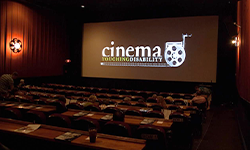 A dark movie theater shows the Cinema Touching Disability logo on its screen