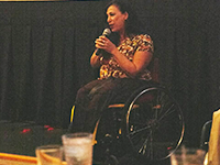 A woman sitting in a wheelchair holds a microphone close to her face with both hands.