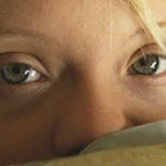 Close up on a young woman's face with strands of blonde hair and green eyes. She has green blankets pulled up to her nose and stares directly at the camera.