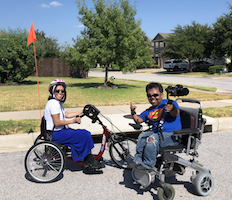 On a bright residential street corner, woman in a sit-down bike and a man in a power chair with video camera rig smile excitedly at the camera. He's giving the shaka sign.