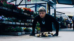 Shot from a low angle, a young man with no legs and a determined expression leans forward on a skateboard as he propels himself with his hands.