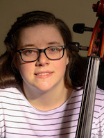 A young woman in glasses smiles placidly at the camera. The bow a cello is visible in front of her shoulder.