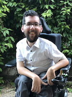 Surrounded by leafy bushes, a smiling man with a beard and glasses leans forward to the camera in his power chair.