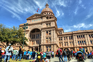 A crowd of people, many wearing yellow caps, stand or sit in front of the Texas Capitol, which stretches in a bright blue sky.