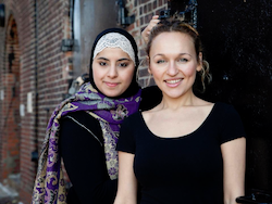 two women stand close together against a brick wall, smiling at the camera. One wears a hijab