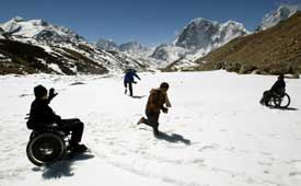 On a flat, snowy field with mountains in the background, four people play in the snow. One chases another on foot, while two in wheelchairs watch and wave from either side.