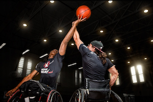 two wheelchair basketball players at tip off in a dark arena, one facing toward the camera, the other with his back to the camera, each reaching for the ball in the air.