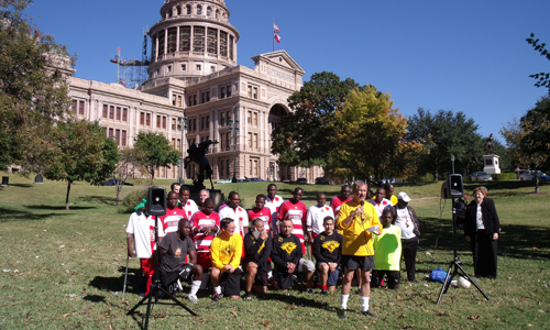 group of soccer players pose together while a man speaks into a microphone, with Texas state capitol in the background
